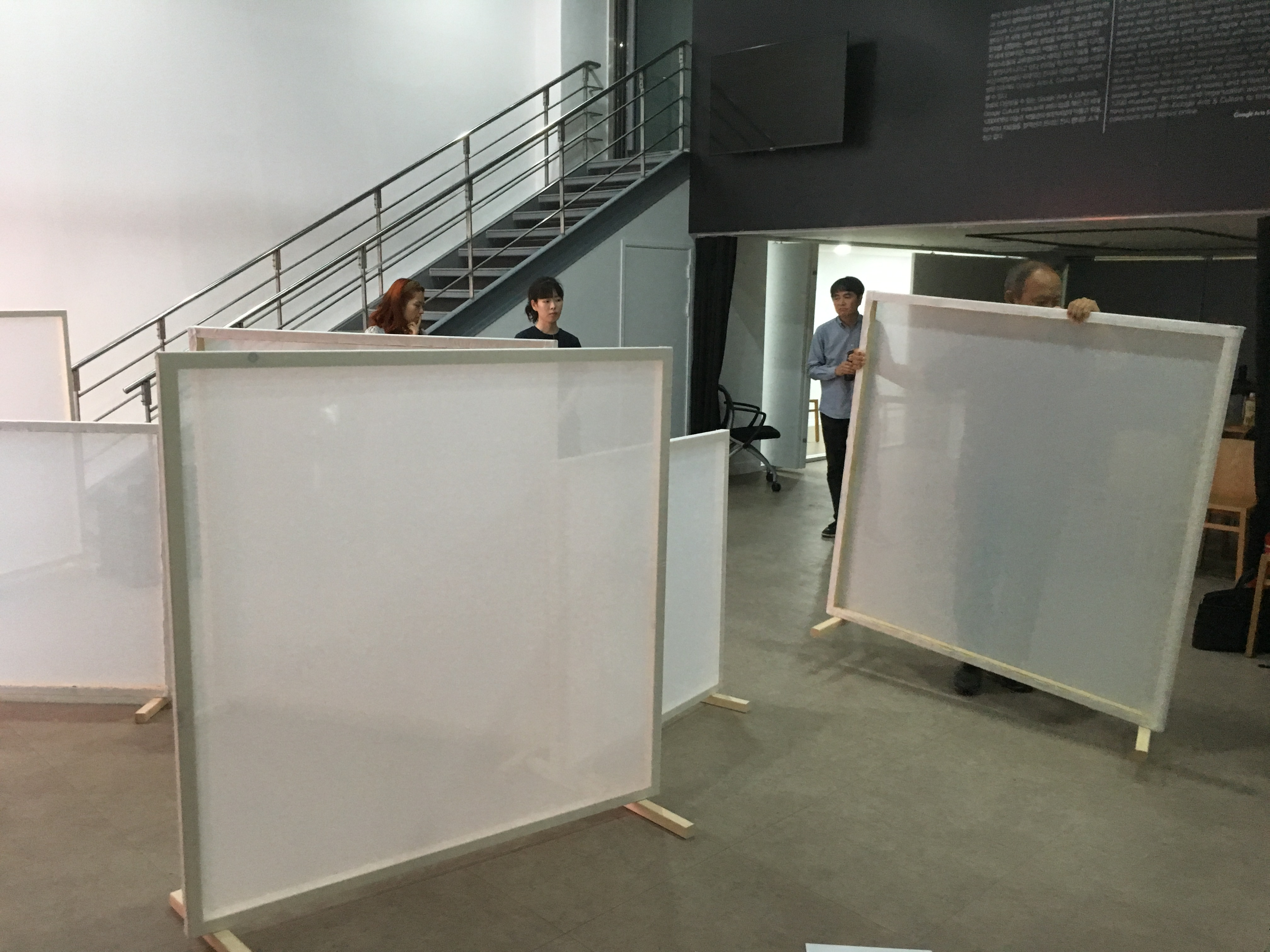 People move wood and fabric screens around a large room