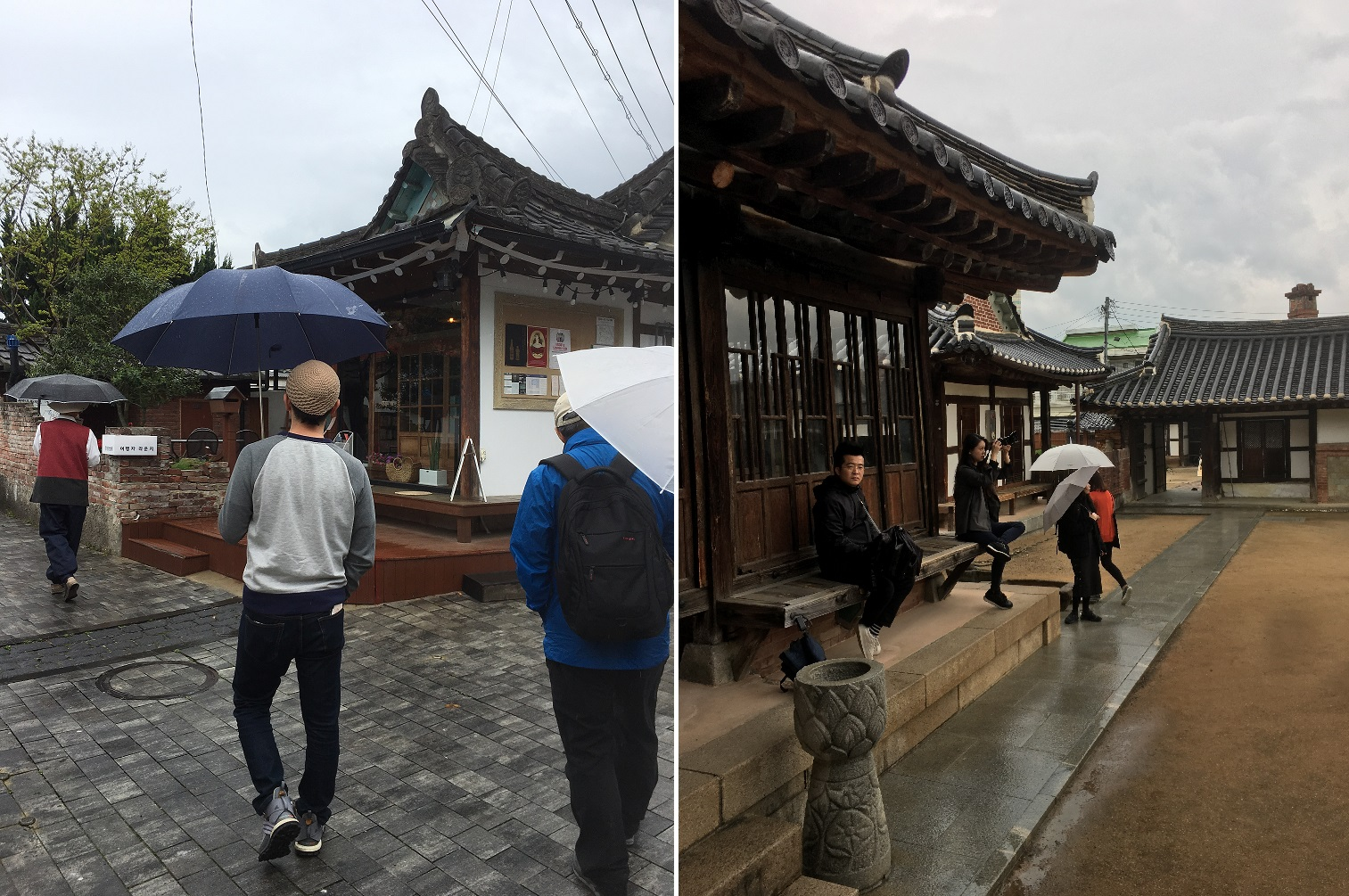 People with umbrellas walk through traditional Korean buildings