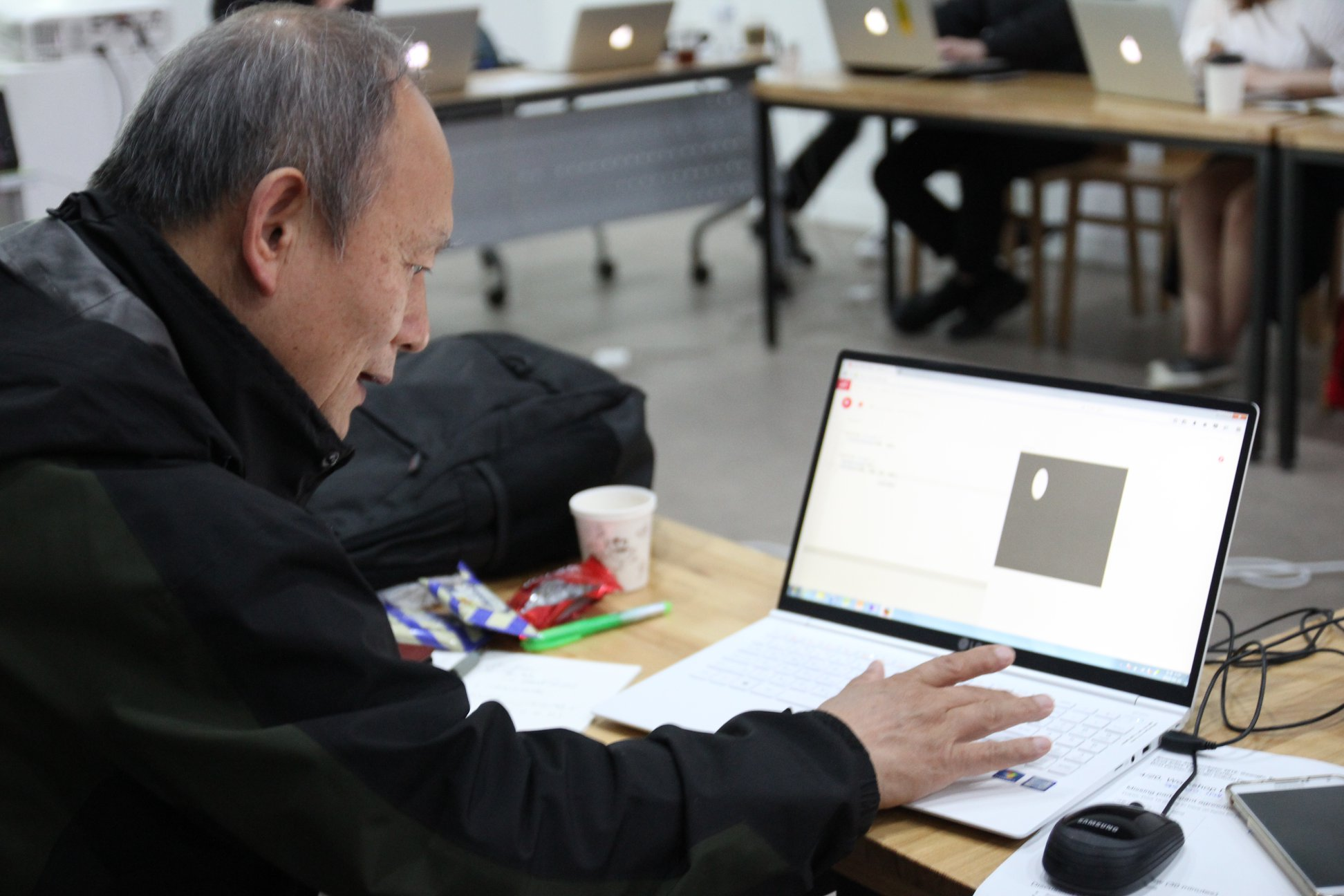 Man looks at computer screen creating a circle with code