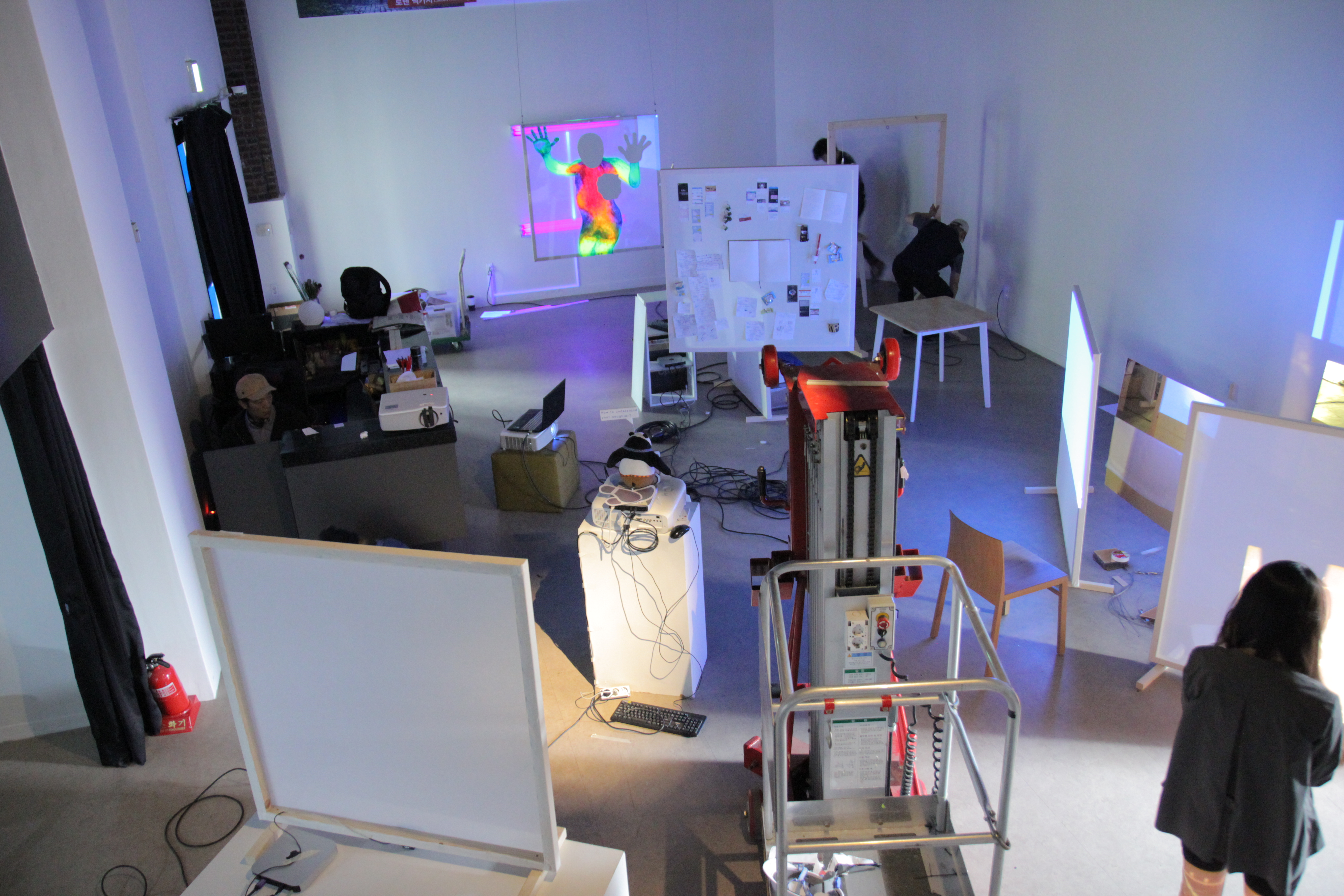 Room filled with screens, equipment, projections, and people
