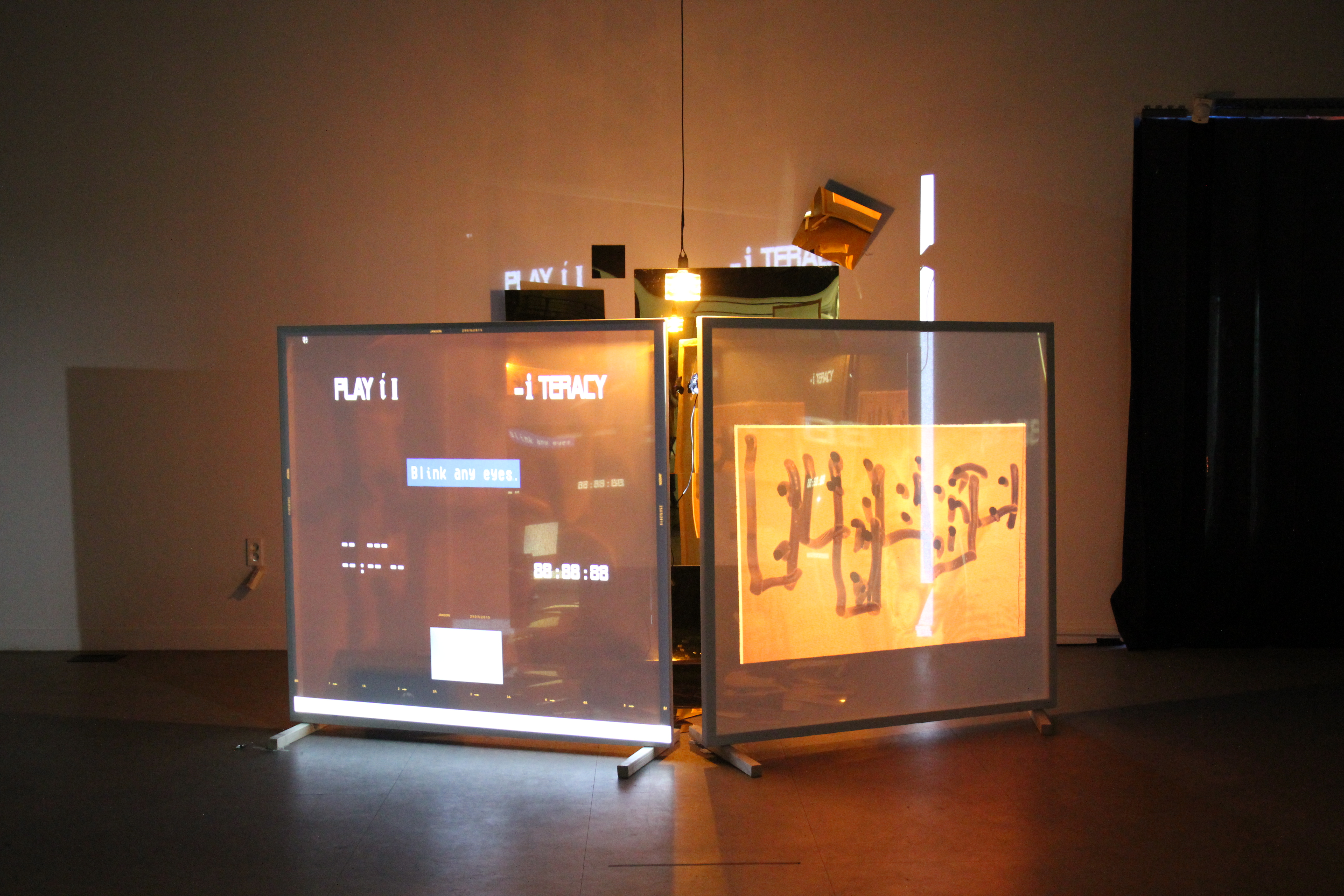 Two screens display projections of scrambled text, lit from behind by reflective metal and light