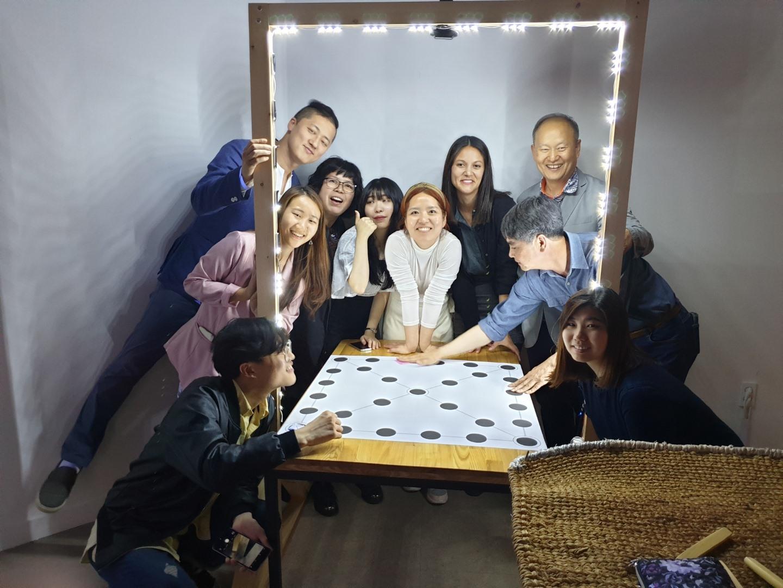 Group gathers around yutnori gameboard lit by LED frame