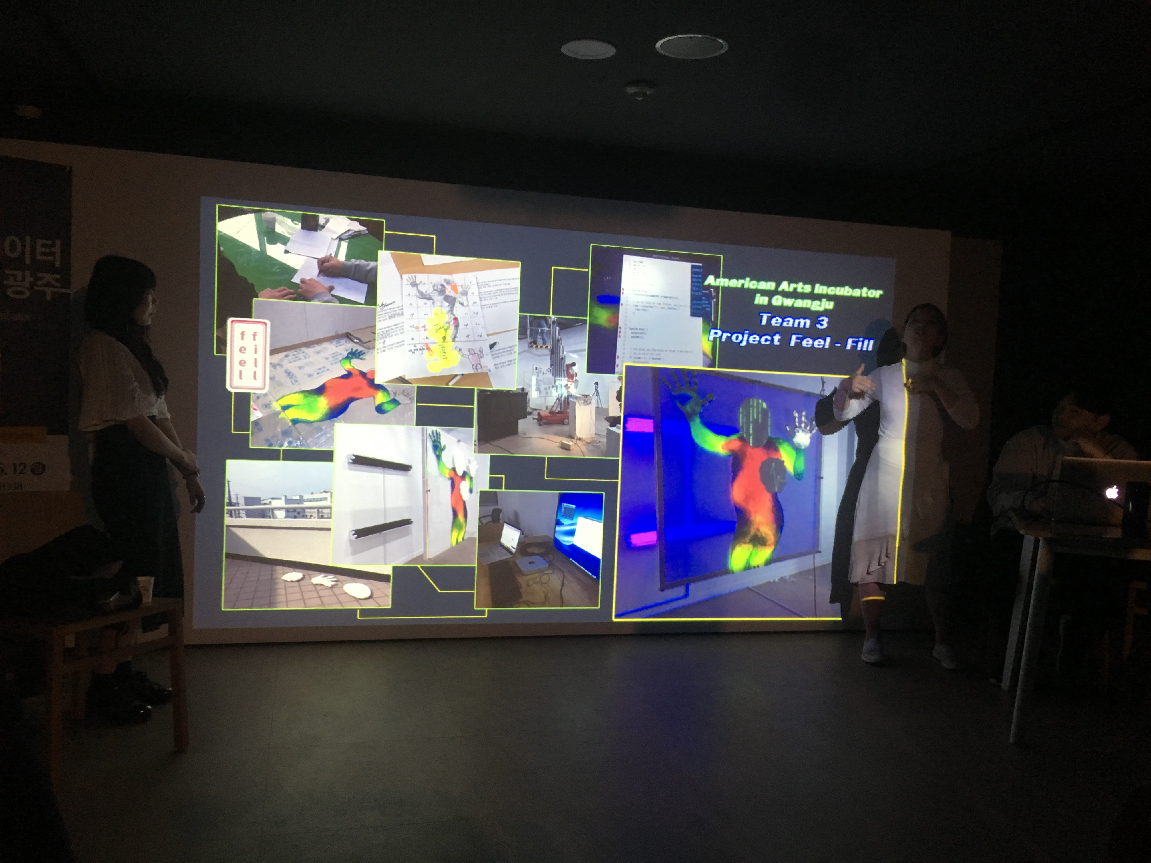 Two participants present in front of a projection of their work featuring bodies, colors, and sketches